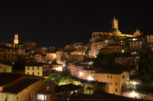 Old town Siena and the Duomo lit up at night.